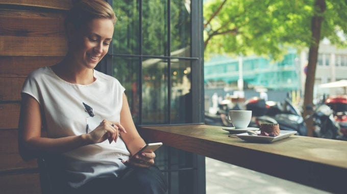 Charming Woman With Beautiful Smile Reading Good News On Mobile Phone
