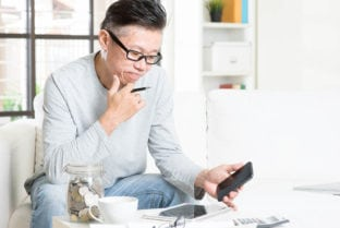 Mature 50s Asian Man Doing Analysis On His Business Budget, Look